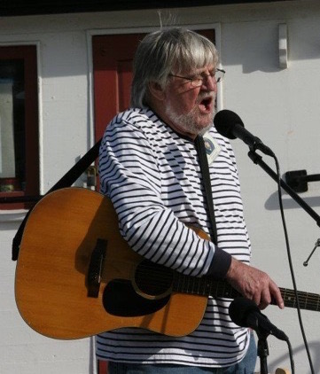 Image of Dick in a striped shirt standing up and singing into a microphone. He is wearing a guitar.