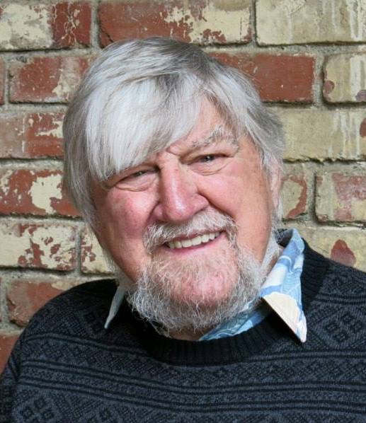 Headshot of Dick looking into the camera and smiling. He has facial hair and is in front of a brick wall.