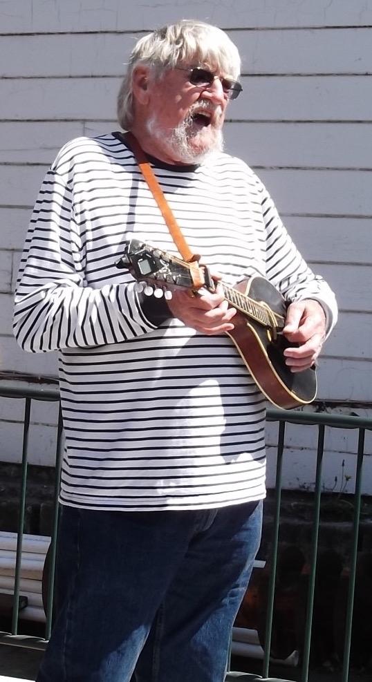 Image of Dick singing and playing mandolin.