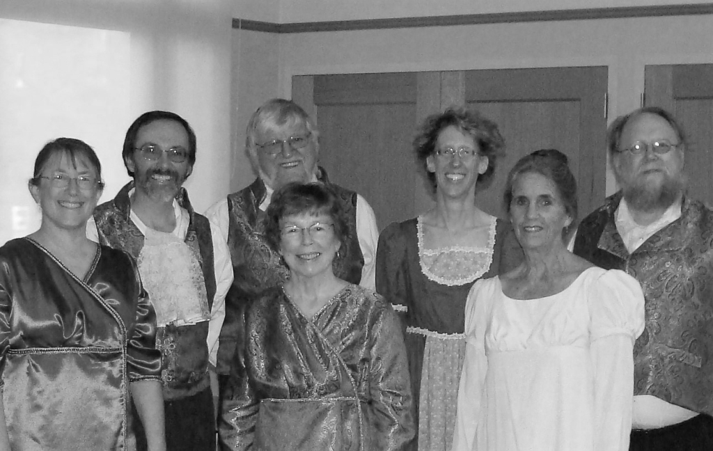 Black and white image of a group of people looking at the camera and smiling. They are dressed in period clothing.