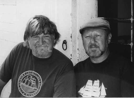 A photo of Holdstock and MacLeod. Black and white image of two men looking at the camera, both with beards, one is wearing a hat.