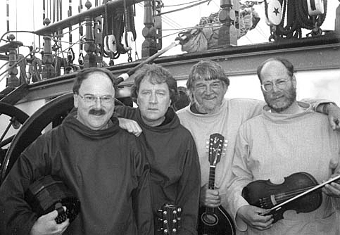 Black and white image of 4 men on a ship looking at the camera. They are all holding musical instruments.