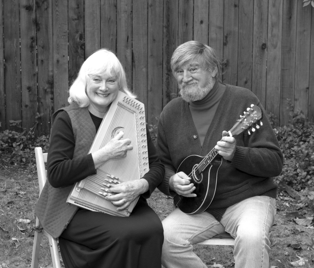 Black and white image of a woman and a man sitting down and looking at the camera and smiling. They are both holding musical instruments.